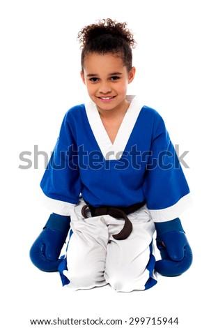 Happy karate girl sitting on floor after practice - stock photo