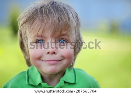 Happy kid against green natural background - stock photo