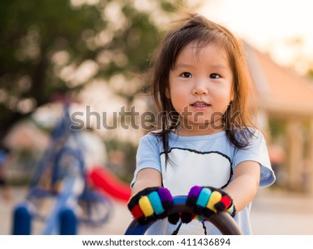 Happy kid, asian baby child playing on a seesaw in sunset light