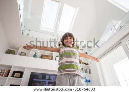 Happy kid at home with hands up