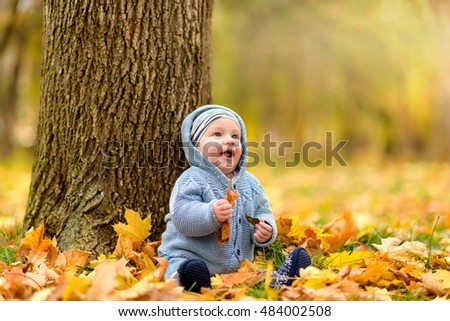Happy Kid at the Park sitting on Autumn Leaves