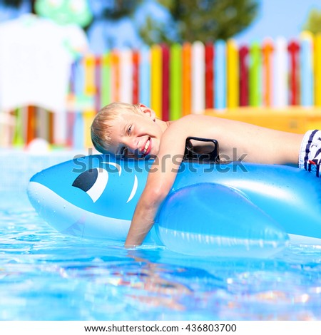 Happy kid, blonde caucasian boy, having fun floating and sliding in water park on inflatable dolphin toy enjoying sunny summer vacations in tropical resort - stock photo