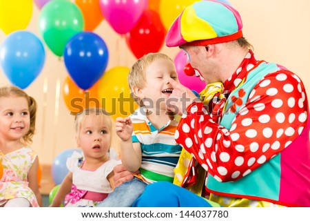 happy kid boy and clown on birthday party - stock photo