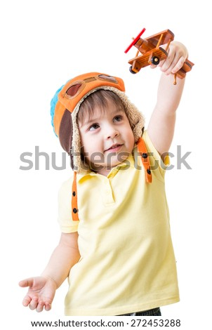 happy kid boy dreams to be pilot playing with wooden airplane toy - stock photo