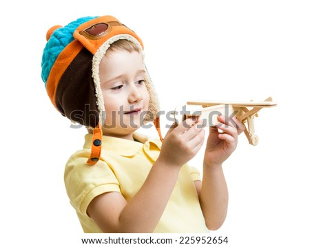 happy kid boy dressed pilot and looking at wooden airplane toy - stock photo