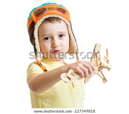 happy kid boy dressed pilot and playing with wooden airplane toy - stock photo