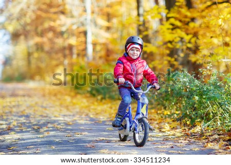 Happy kid boy having fun in autumn forest with a bicycle. Active child wearing bike helmet. Safety, sports, leisure with kids concept. - stock photo