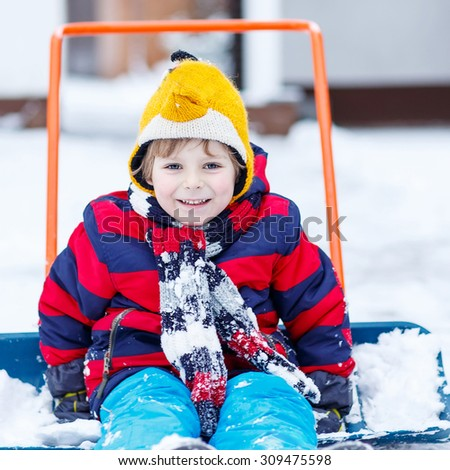 Happy kid boy having fun with riding on snow shovel , outdoors  on cold day. Active outdoors leisure with children in winter. - stock photo