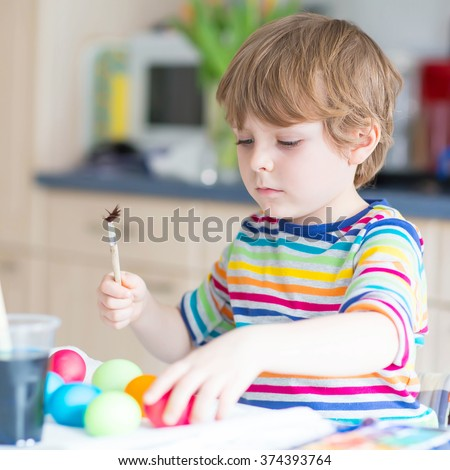 Happy kid boy of 4 years coloring eggs for Easter holiday in domestic kitchen, indoors. Child having fun and celebrating feast. - stock photo