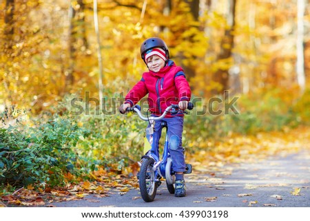 Happy kid boy of 3 years having fun in autumn forest with a bicycle on beautiful fall day. Active child wearing bike helmet. Safety, sports, leisure with kids concept. - stock photo