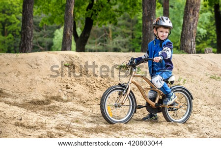 Happy kid boy of 4 years having fun in autumn or summer forest with a bicycle on beautiful fall or spring day. Active child making sports. Safety, sports, leisure with kids concept. - stock photo