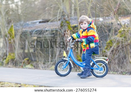 Happy kid boy on new bicycle, having fun on cold  day, outdoors. Active leisure with children in winter, sping or autumn. - stock photo