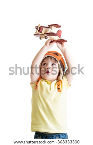 happy kid boy pilot and playing with wooden airplane toy - stock photo