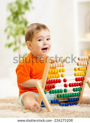 happy kid boy playing with abacus toy indoors