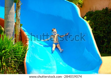 happy kid boy sliding in tropical water park - stock photo