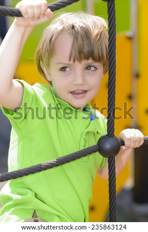 Happy kid climbing on rope ladder - stock photo