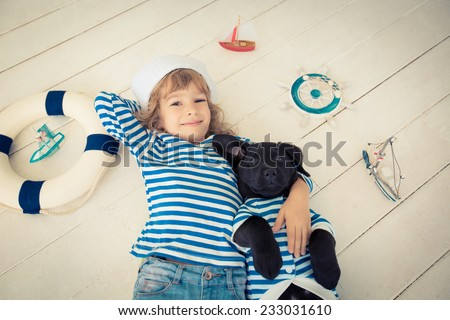 Happy kid dressed in sailor. Child playing with dog at home. Travel and adventure concept - stock photo
