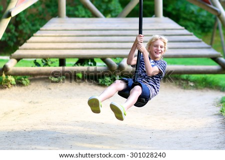 Happy kid enjoying active summer vacation. Adorable child, blond smiling schoolboy, having fun outdoors swinging on playground in the park on a sunny day. - stock photo