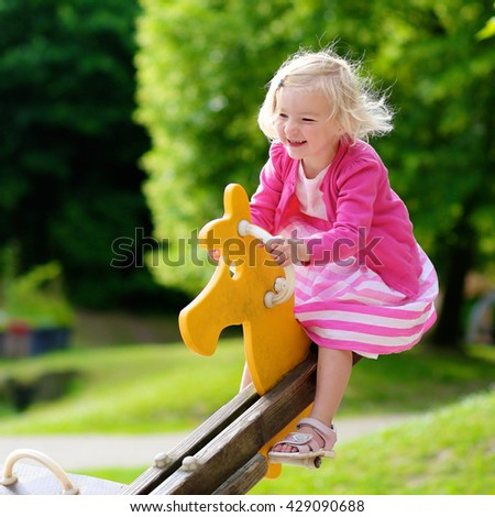 Happy kid enjoying active summer vacation. Adorable little child, blond cute toddler girl, having fun outdoors swinging on playground in the park on a sunny day. - stock photo