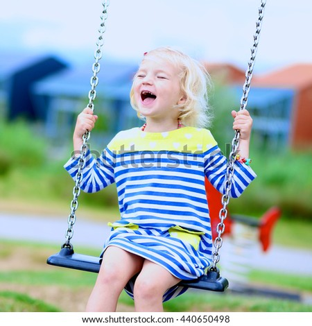 Happy kid enjoying active summer vacation. Adorable little child, blond cute toddler girl, having fun outdoors swinging on playground in the park on a sunny day - stock photo