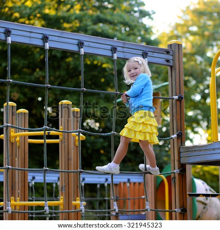 Happy kid enjoying activity in the park. Adorable little child, blond cute toddler girl, having fun outdoors climbing on playground on a sunny day