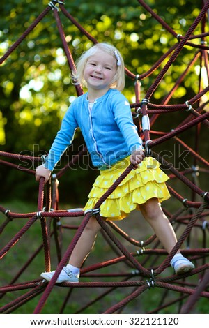 Happy kid enjoying activity in the park. Adorable little child, blond cute toddler girl, having fun outdoors climbing on playground on a sunny day - stock photo