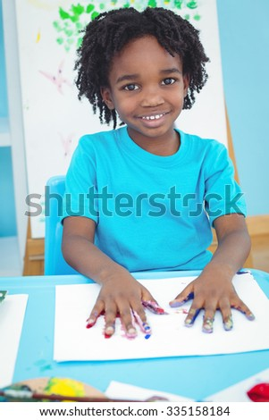 Happy kid enjoying arts and crafts painting with his hands - stock photo