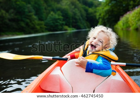 Happy kid enjoying kayak ride on beautiful river. Little curly toddler boy kayaking on hot summer day. Water sport and camping fun. Canoe for children. Funny child with vessel in a boat.