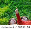 Happy kid enjoying sunny late summer and autumn day in nature on green grass - stock photo