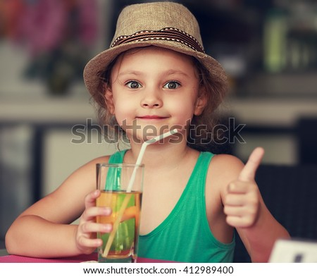 Happy kid girl drinking apple juice in restaurant and showing thumb up sign - stock photo
