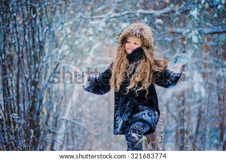 happy kid girl having fun and jumping in snowy winter forest - stock photo