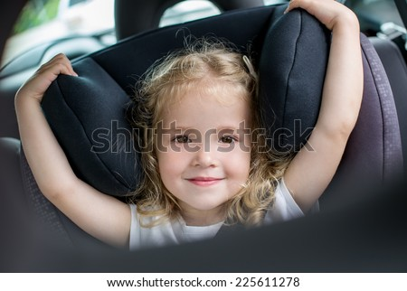happy kid girl in the car seat - stock photo