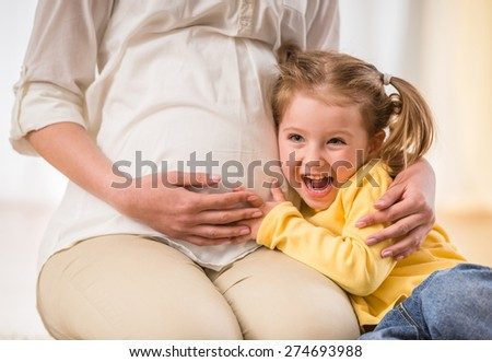 Happy kid girl is hugging pregnant mother's belly. - stock photo