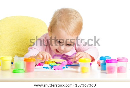 Happy kid girl playing with colorful clay toy - stock photo
