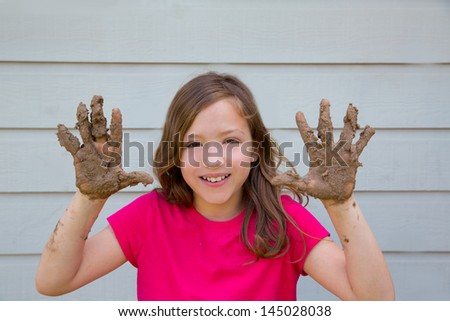 happy kid girl playing with mud with dirty hands smiling portrait - stock photo