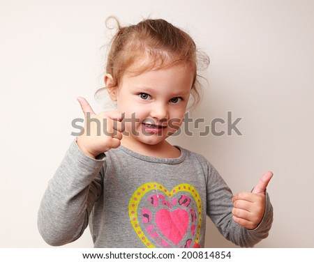 Happy kid girl showing thumbs up sign. Ok symbol - stock photo