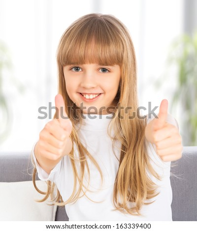 happy kid girl shows a thumbs up - stock photo