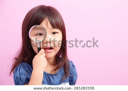 Happy kid girl smile and hold magnifier isolated on pink background, asian - stock photo