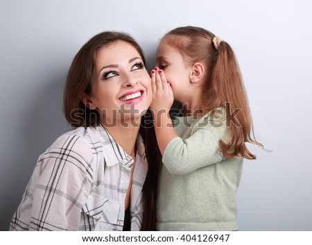 Happy kid girl whispering the secret to her smiling mother in ear with fun face on blue background