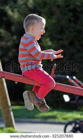 Happy kid having fun in the playground - stock photo