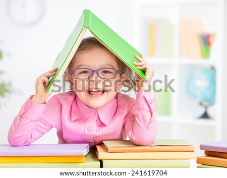 Happy kid in glasses under roof made from book - stock photo