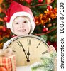 Happy kid in Santa`s hat holding old wooden clock against decorated Christmas background - stock photo