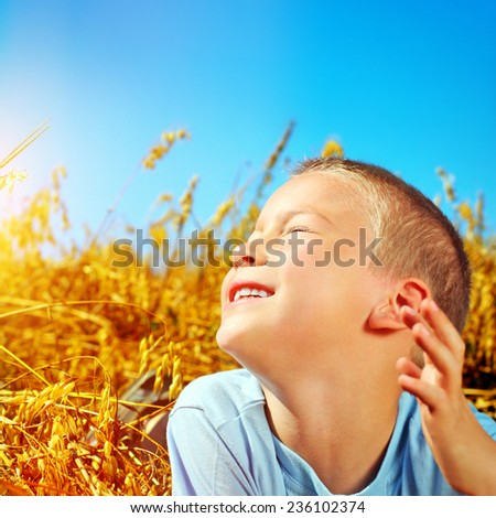 Happy Kid in the Summer wheat field - stock photo