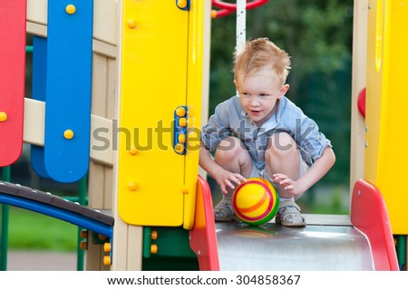 Happy kid is playing on slide