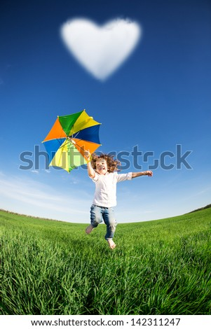 Happy kid jumping in green field against blue sky. Summer vacation concept