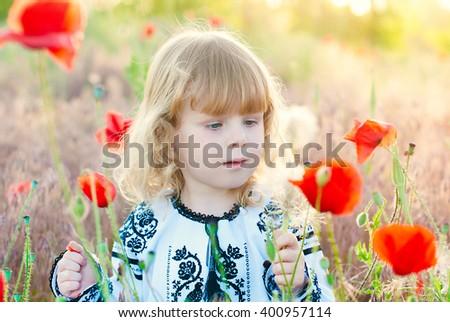 Happy Kid. Little Girl having Fun at the Summer Poppies Field. Sunshine effects. - stock photo