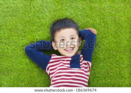 happy kid lying and holding his head on a meadow - stock photo