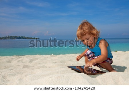 Happy kid on the beach playing tablet PC - stock photo
