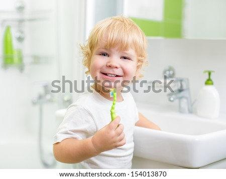 Happy kid or child  brushing teeth in bathroom. Dental hygiene. - stock photo
