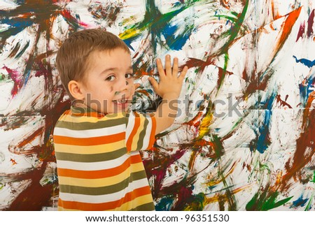 Happy kid painting with his palms a wall and looking back over shoulder